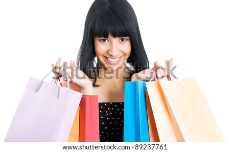 Portrait of a beautiful asian woman with colored shopping bags isolated on white
