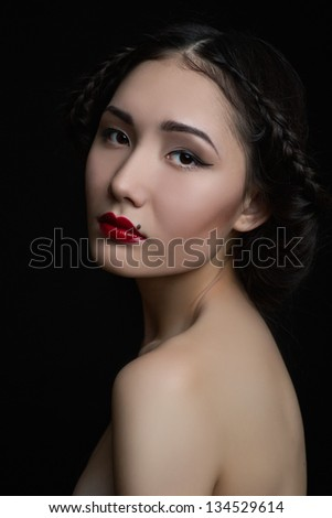 portrait of a beautiful Asian woman with red lips isolated on black studio background
