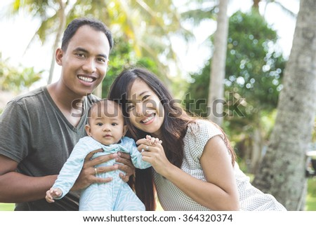 portrait of a beautiful asian young family having fun with his baby on a sunny day - stock photo