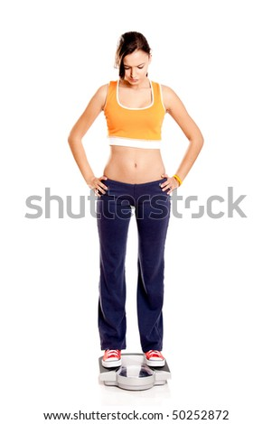Portrait of a beautiful athletic girl checking her weight, isolated on white - stock photo