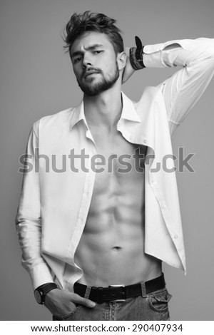 Portrait of a beautiful athletic man in white shirt and jeans in the studio, black and white photo - stock photo