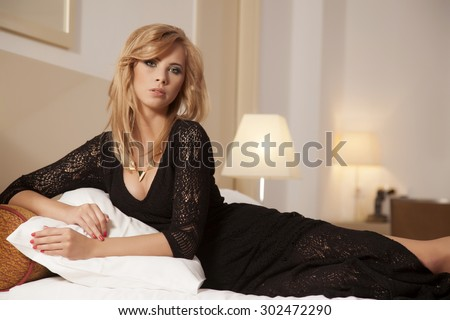 Portrait of a beautiful attractive and sexy young adult sensuality pretty blonde woman wearing elegance fashionable dress on bed in bedroom
