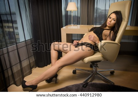 Portrait of a beautiful attractive and sexy young adult sensuality pretty brunette woman in black lingerie on the armchair in luxury apartment - stock photo