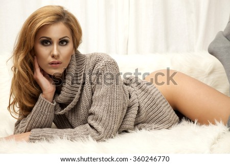 Portrait of a beautiful attractive and sexy young adult sensuality pretty brunette woman in gray sweater and white socks lying on the white sofa in fur - stock photo