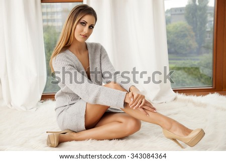 Portrait of a beautiful attractive and sexy young adult sensuality pretty brunette woman in grey sweater on the window on luxury apartment - stock photo