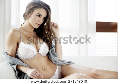 Portrait of a beautiful attractive and sexy young adult sensuality pretty brunette woman in white lingerie and grey sweater on the white couch in morning sunlight window on luxury style apartment - stock photo