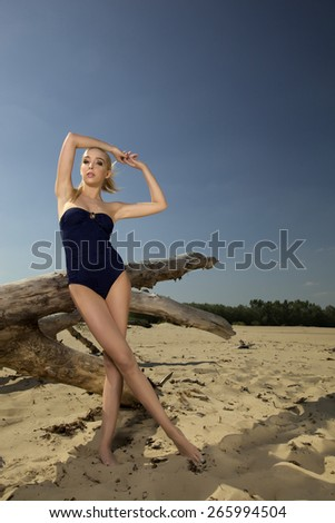 Portrait of a beautiful attractive sensuality young adult sexy pretty blonde woman in black swimwear posing on the beach - stock photo