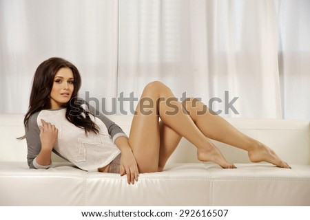 Portrait of a beautiful attractive sexy and sensuality young adult pretty blonde woman long legs in grey sweater on the white couch