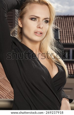 Portrait of a beautiful attractive slim sexy and sensuality young adult blonde woman in elegance black dress on the morning sunlight balcony