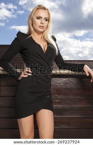 Portrait of a beautiful attractive slim sexy and sensuality young adult blonde woman in elegance black dress on the morning sunlight balcony - stock photo