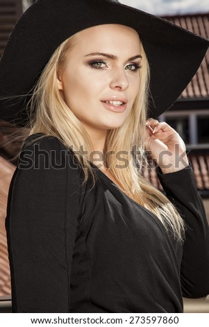 Portrait of a beautiful attractive slim sexy and sensuality young adult blonde woman in elegance black dress and hat on the morning sunlight balcony - stock photo