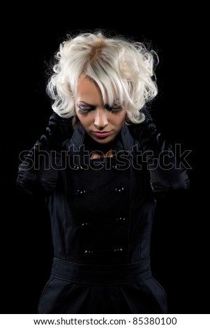 Portrait of a beautiful attractive woman with make up and hair style hold hand cover ear over black background