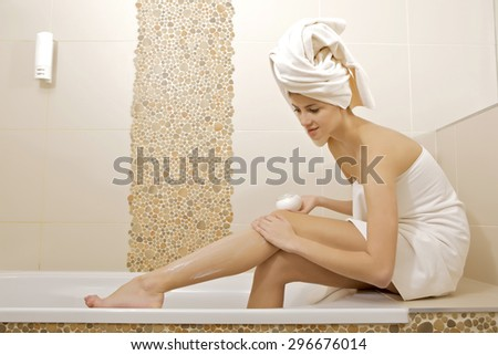 Portrait of a beautiful attractive young adult pretty brunette woman applying moisturizer cream on the legs in bathroom - stock photo