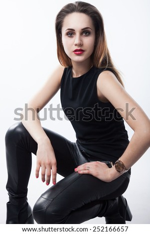Portrait of a beautiful attractive young business woman standing against white background. Girl wearing in black. Perfect makeup, red lips, straight long hair.