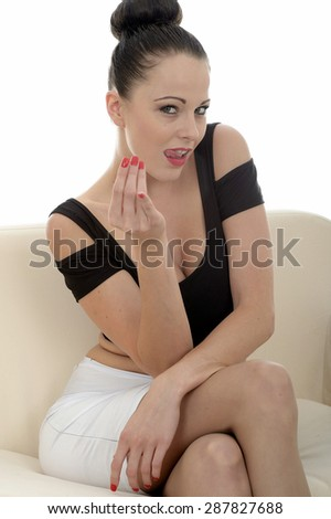 Portrait Of A Beautiful Attractive Young Caucasian Woman Relaxing And Posing On A Sofa Or Couch Beckoning To Come Over With Her Hand - stock photo