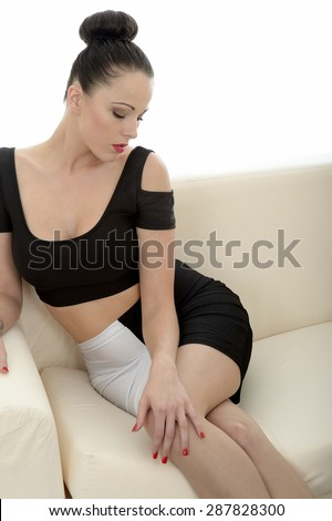 Portrait Of A Beautiful Attractive Young Caucasian Woman Relaxing And Posing On A Sofa Or Couch Teasing And Looking Very Seductive - stock photo