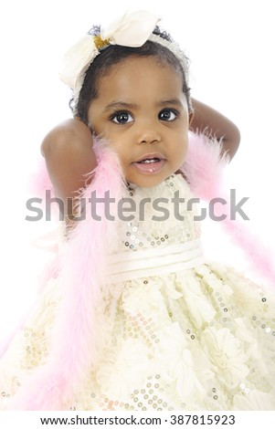 Portrait of a beautiful baby girl all dressed up in a white hair bow, sequin dress and pink boa.  On a white background.