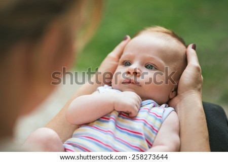Portrait of a beautiful baby lying in his loving mother's lap looking at her with big blue eyes with garden background - stock photo