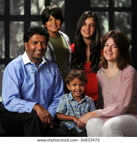 Portrait of a beautiful biracial family of five, framed by a multi-pane winter window. - stock photo