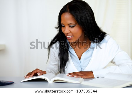 Portrait of a beautiful black girl studying at soft colors composition - stock photo