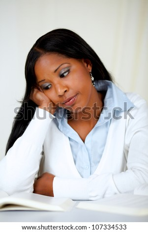 Portrait of a beautiful black tired woman learning at soft colors composition
