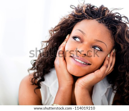 Portrait of a beautiful black woman daydreaming - stock photo