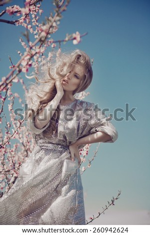 Portrait of a beautiful blode girl in a silver dress, posing in a flowering cherry orchard - stock photo