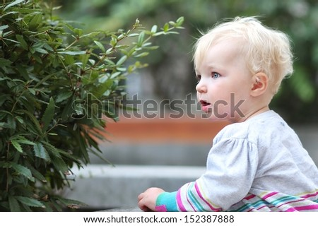 Portrait of a beautiful blond baby girl, standing outdoors next to the bushes - stock photo