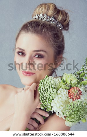 Portrait of a beautiful blond bride with a diamante headpiece. Hair in romantic top knot bun hairstyle. Wedding flowers.  - stock photo