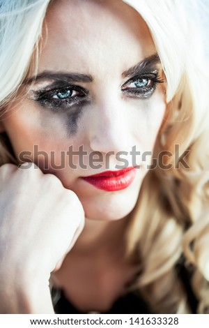 portrait of a beautiful blond caucasian girl resting her head on her fist with her black glitter make-up smudged down her cheeks - stock photo