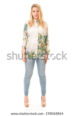 Portrait of a beautiful blond teenage girl wearing blue trousers, a flowery white shirt and pink high heels isolated against a white background - stock photo