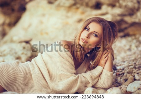 Portrait of a beautiful blond woman in a sweater in autumn outdoors - stock photo