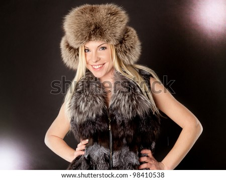 portrait of a beautiful blond woman wearing fur coat and hat - stock photo