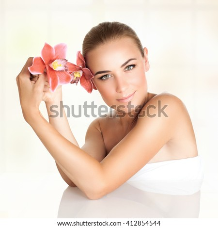 Portrait of a beautiful blond woman with orchid flowers in the head and hand spending day at spa salon, beauty and health treatment - stock photo