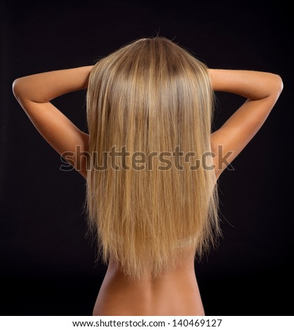 portrait of a beautiful blond woman with perfect shiny hair on black background