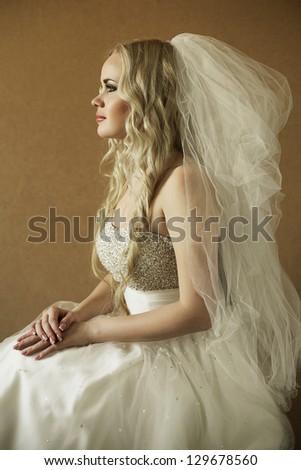 portrait of a beautiful blonde bride over wooden background. daylight. studio shot - stock photo