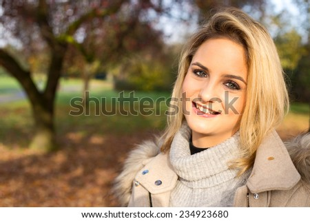 portrait of a beautiful blonde girl in a park. - stock photo