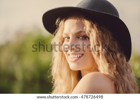 Portrait of a beautiful blonde girl in the hat smiling on the background of nature