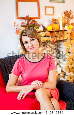 portrait of a beautiful blonde girl in the red blouse and autumn interior room