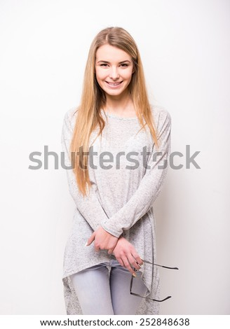 Portrait of a beautiful blonde girl is holding sunglasses is smiling while standing on the white background. - stock photo