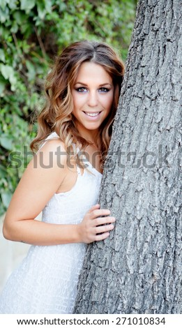 Portrait of a beautiful blonde girl next to a tree - stock photo