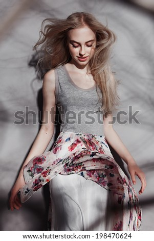 Portrait of a beautiful blonde girl, standing in the shadows of a tree, with developing hair - stock photo