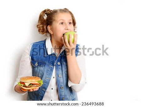 portrait of a beautiful blonde girl, teenager and schoolgirl, holding a hamburger and apple on a white background  - stock photo