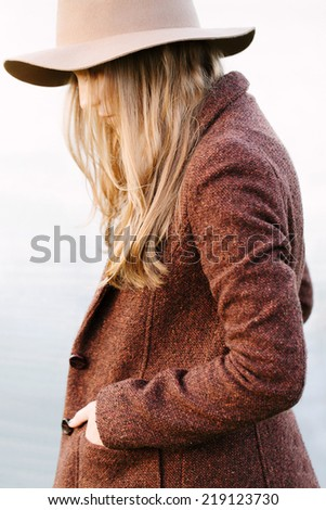 Portrait of a beautiful blonde girl walking down lakeside. Profile to camera. Wearing hat and jacket. Outside - stock photo