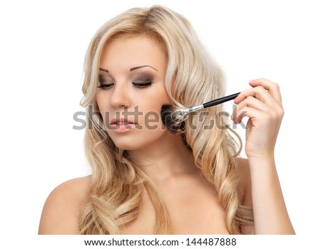 portrait of a beautiful blonde girl who is holding a makeup brush