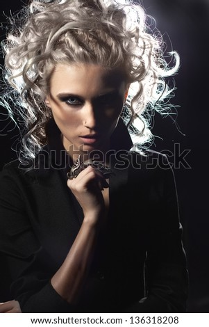 Portrait of a beautiful blonde girl with an unusual ring on the fingerin contrasting light  on a black background