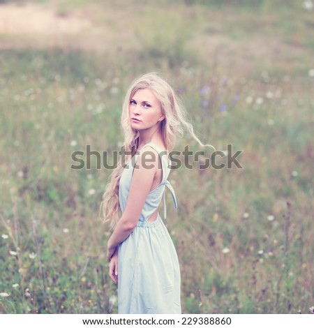 portrait of a beautiful blonde in a field in spring - stock photo