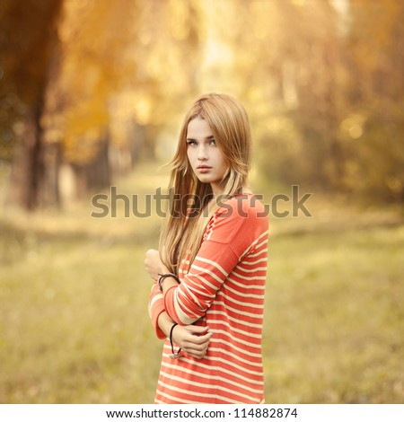 portrait of a beautiful blonde in a park in autumn - stock photo