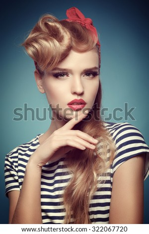 Portrait of a beautiful blonde in pinup style with red scarf on the head. Bright makeup. Red lips. Lashes. - stock photo