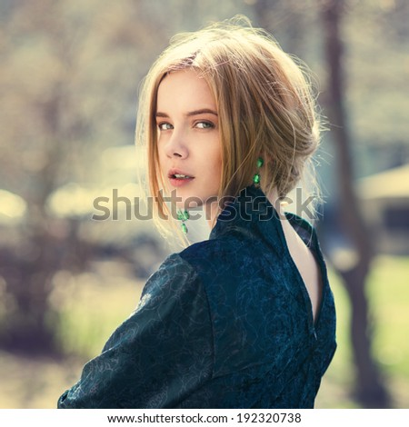 portrait of a beautiful blonde in the spring in the park - stock photo